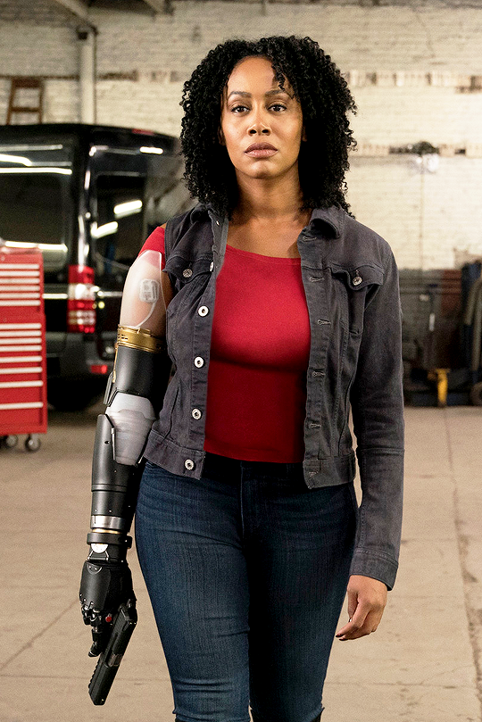 A woman with a bionic arm holds a gun and stares determinedly past the camera